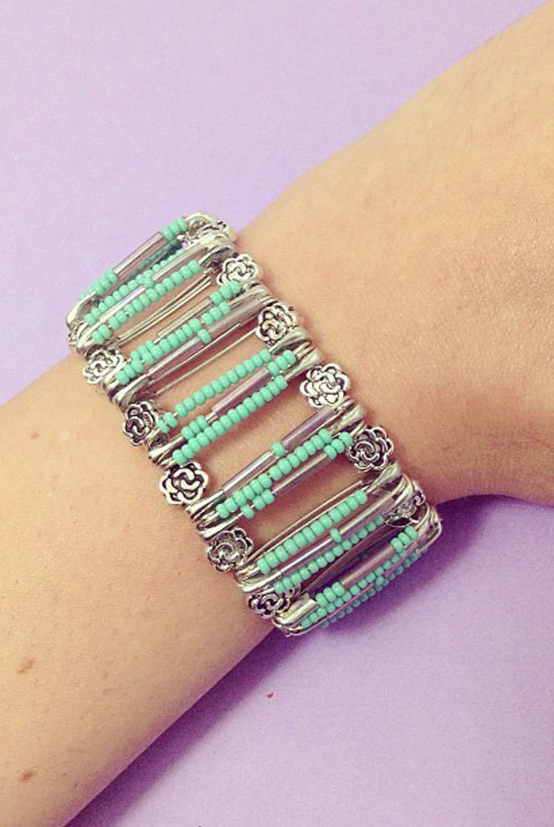 A bracelet made from silver safety-pins, decorated with small green beads