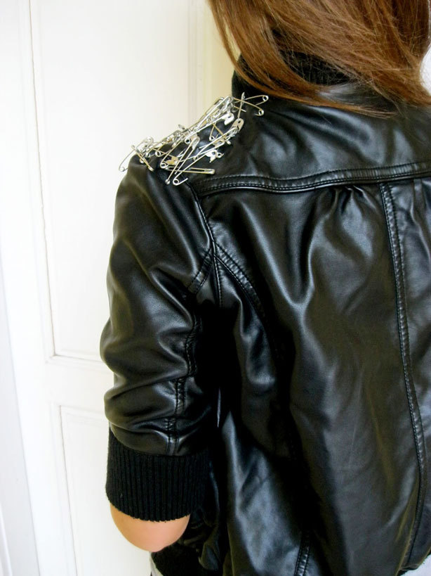A safety-pin fashion black leather jacket, with pins on the shoulders
