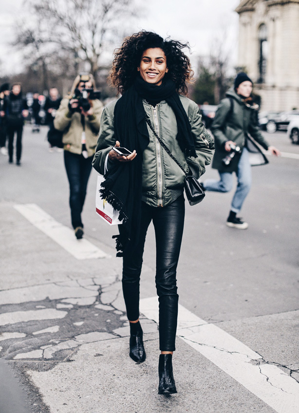 A woman wearing a warm black scarf, khaki bomber jacket and leather trousers as part of a glam punk outfit