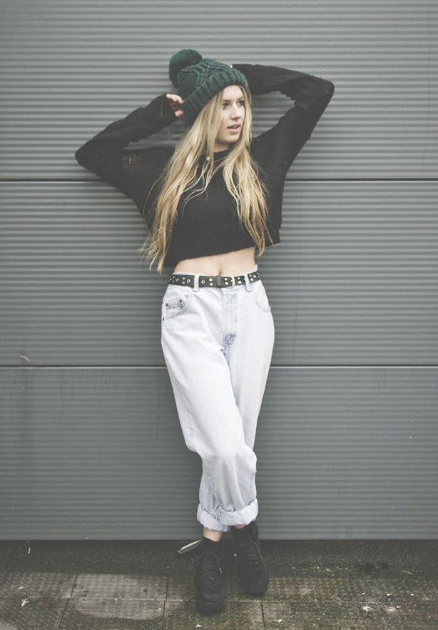 A blonde woman wears a wool style long-sleeved crop top, white jeans and platform shoes as part of a warm punk outfit