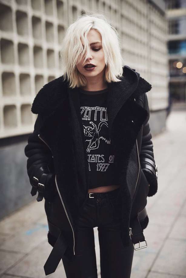 A bleach blond punk woman wearing a black leather jacket, led-zeppelin black t-shirt and black pants