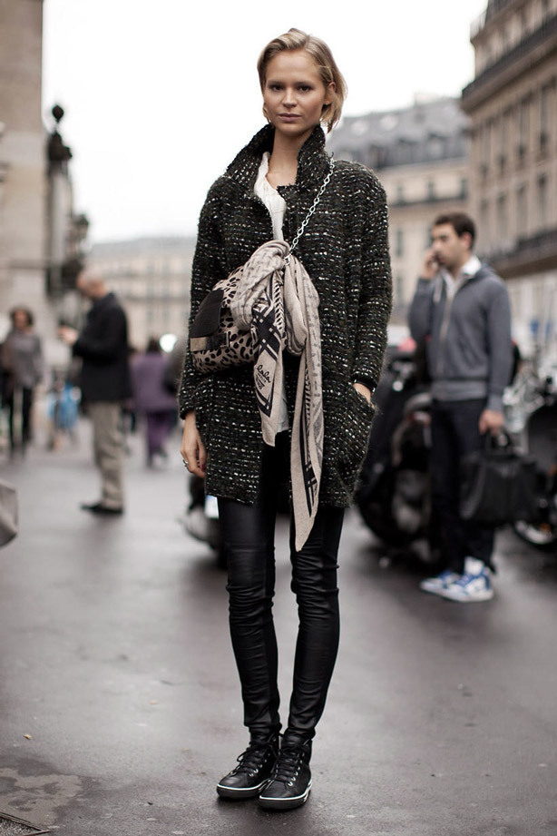 A woman stands in the street, wearing a long wool jacket, leather trousers and punk style platform trainers
