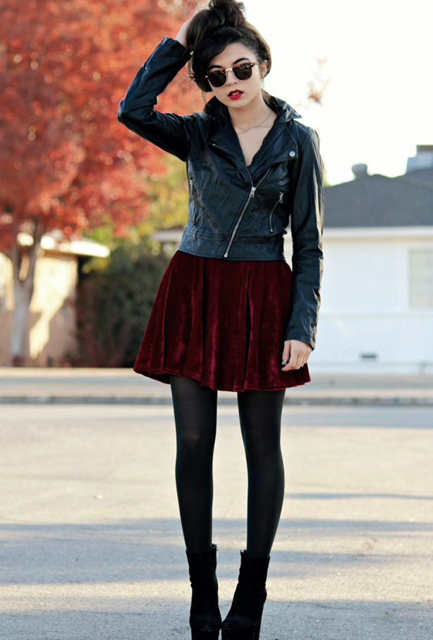 A woman wearing a glamorous punk outfirt, with a red velvet skirt, black leggings, and a black leather jacket