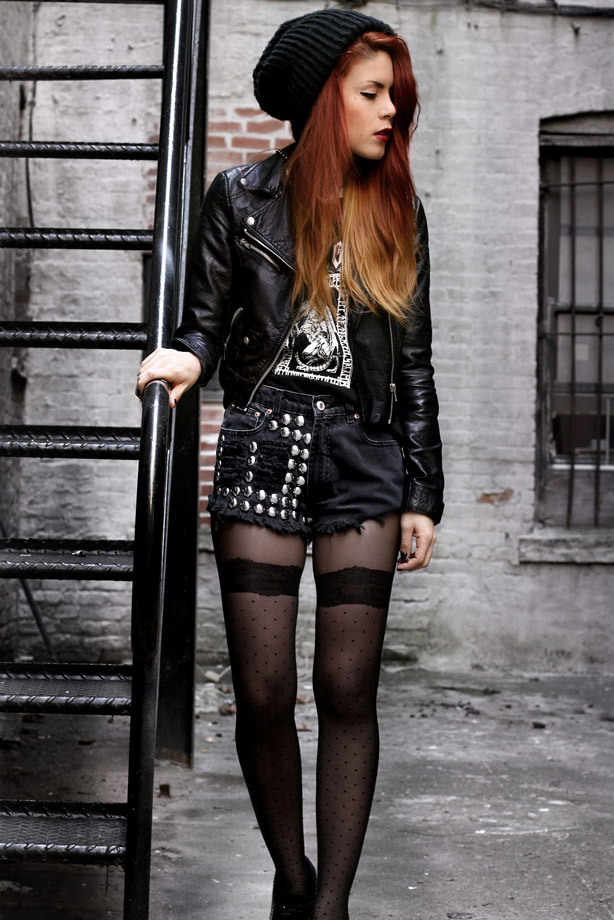 A woman wears black tights with punk style cut-off shorts and a black leather jacket and a black wool hat