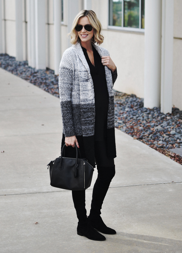 A woman smiles, wearing an oversized cardigan, black full-length leggings and black boots