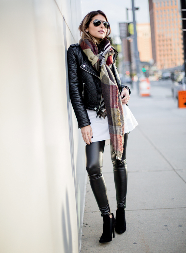 A woman leans against a wall, wearing a white mini skirt and full-length leather leggings with stiletto boots