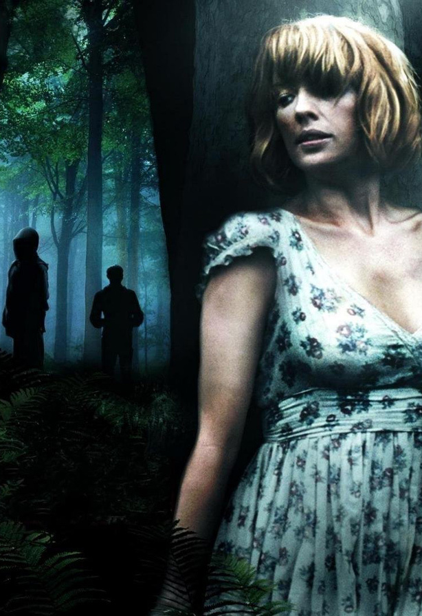 A promotional picture for the survival horror film Eden Lake, with Kelly reilly hiding from spooky figures in the woods