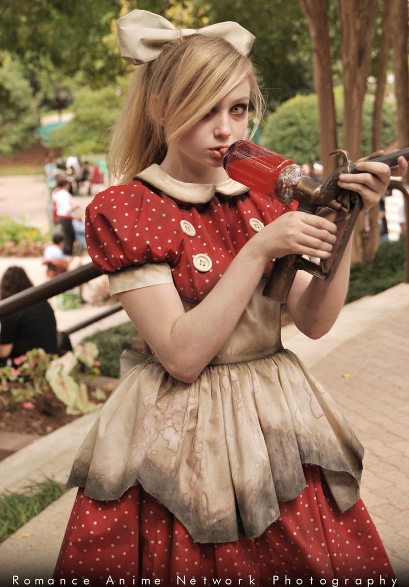 A woman dressed as Little Sister from the game Boishock, wearing a vintage tea dress and pinafore as part of video game fashion