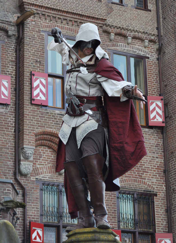A man wearing Assassins Creed fashion cosplay, holding a sword
