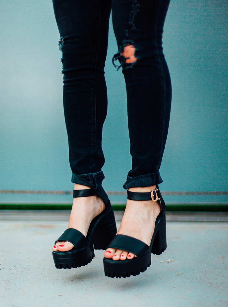 A close up picture of platform sandals with ripped black jeans