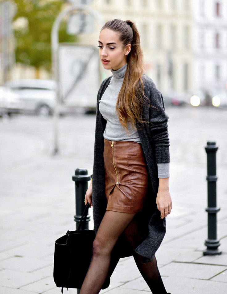 A model wears a cute winter outfit, with a brown pencil skirt and a rollneck top layered with a grey cardigan