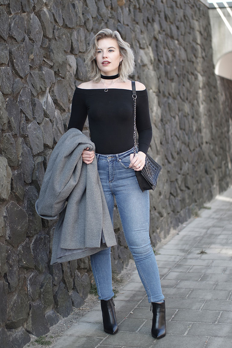 A blonde model wears light denim skinny jeans, a black bodysuit and a black choker with boots