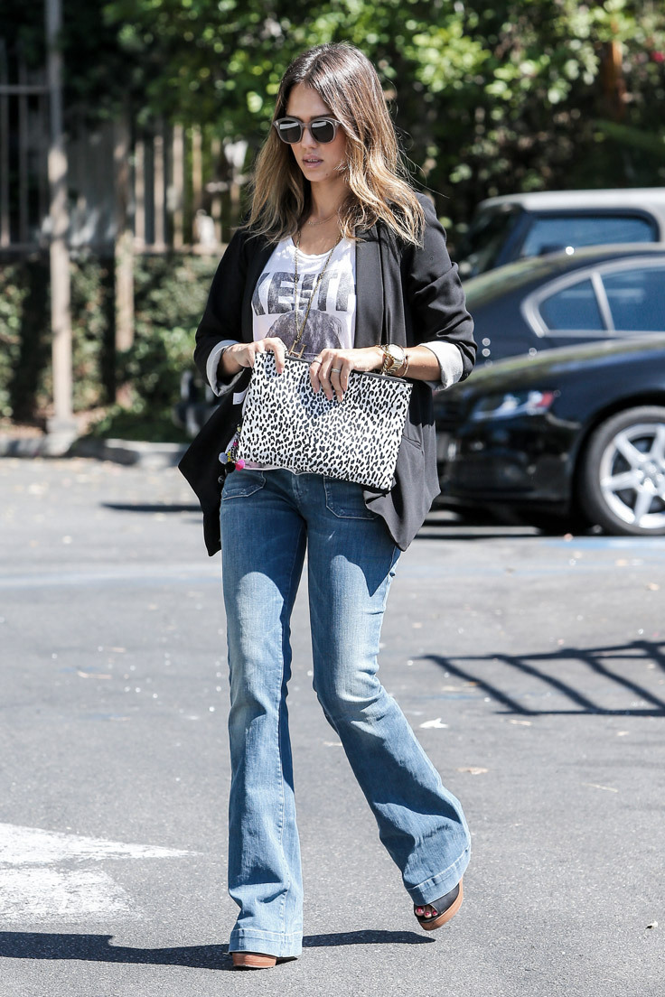 A woman wearing a black jacket and printed tee shirt with boot cut jeans for a pear body shape
