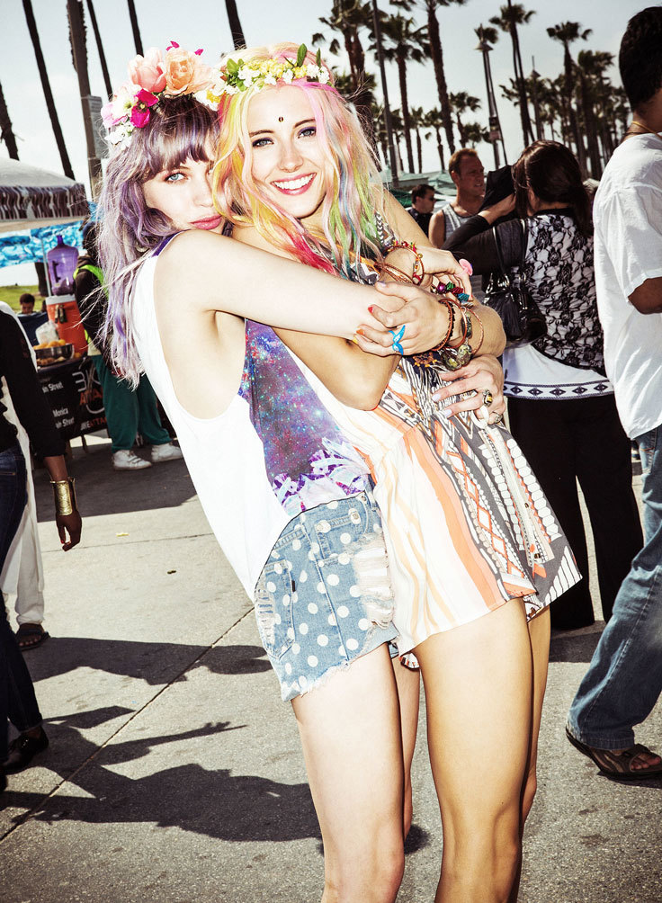 Two women with rainbow hair, wearing flower crowns and boho style at a festival