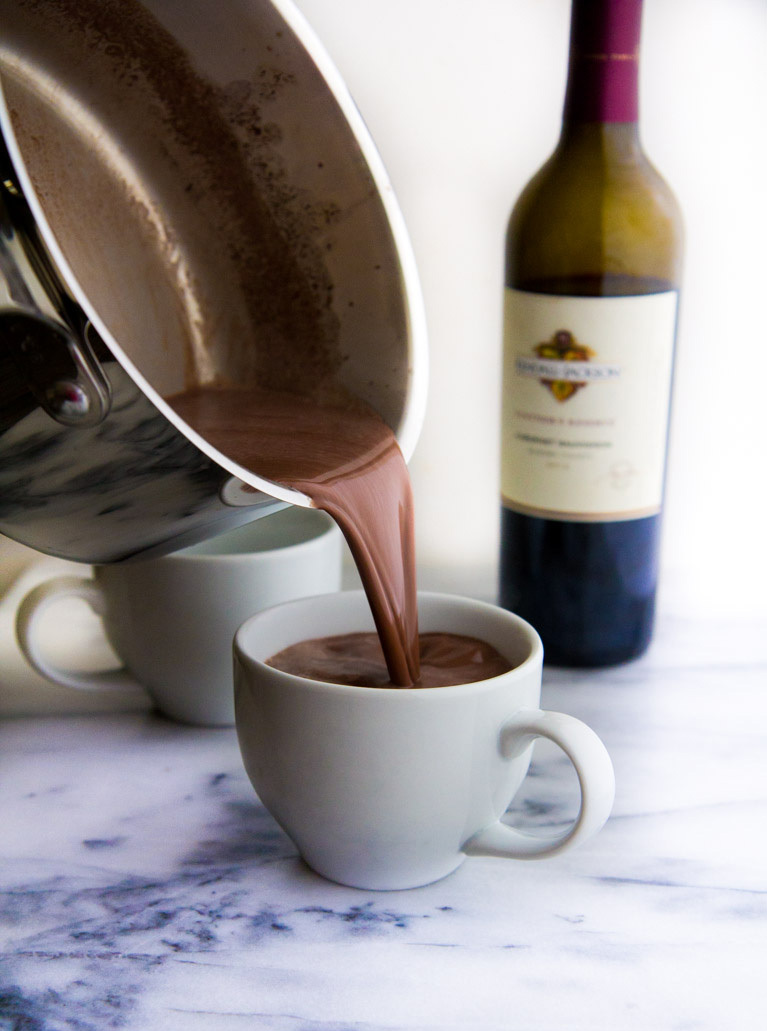 Red wine hot chocolate pouring from a pan into a mug