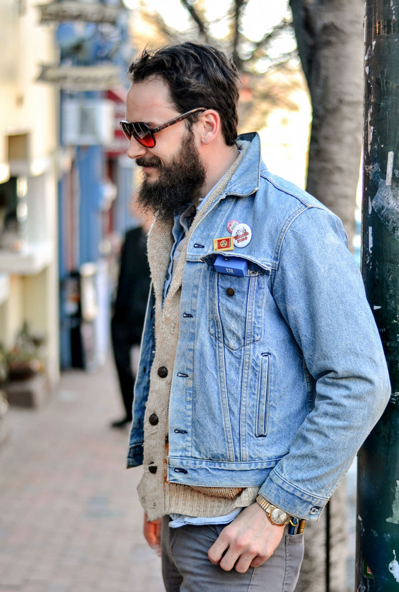 A bearded man wears shades and a denim jacket with cool badges
