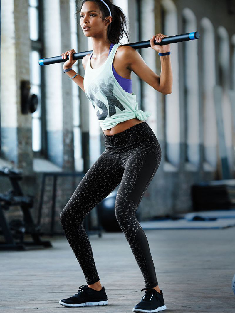 A fitness model doing squats wearing alternative style gymwear, with dark leggings and a slogan tank top