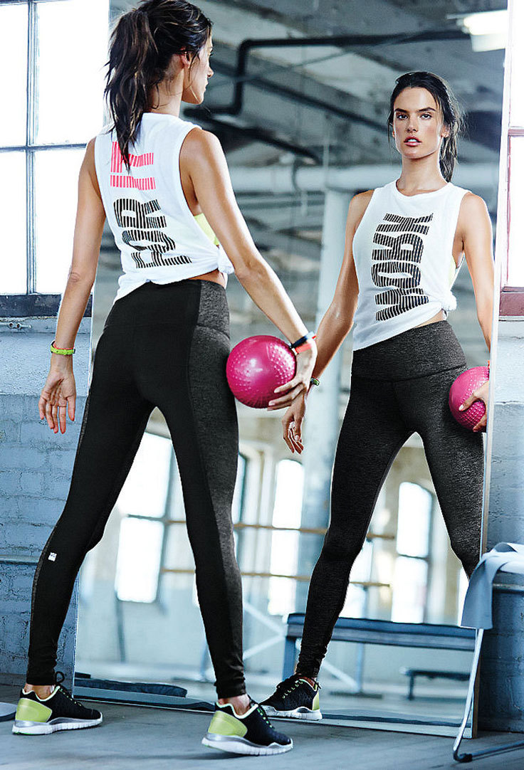 A fitness model wearing dark leggings and a tank top as part of a gym outfit with and alternative style