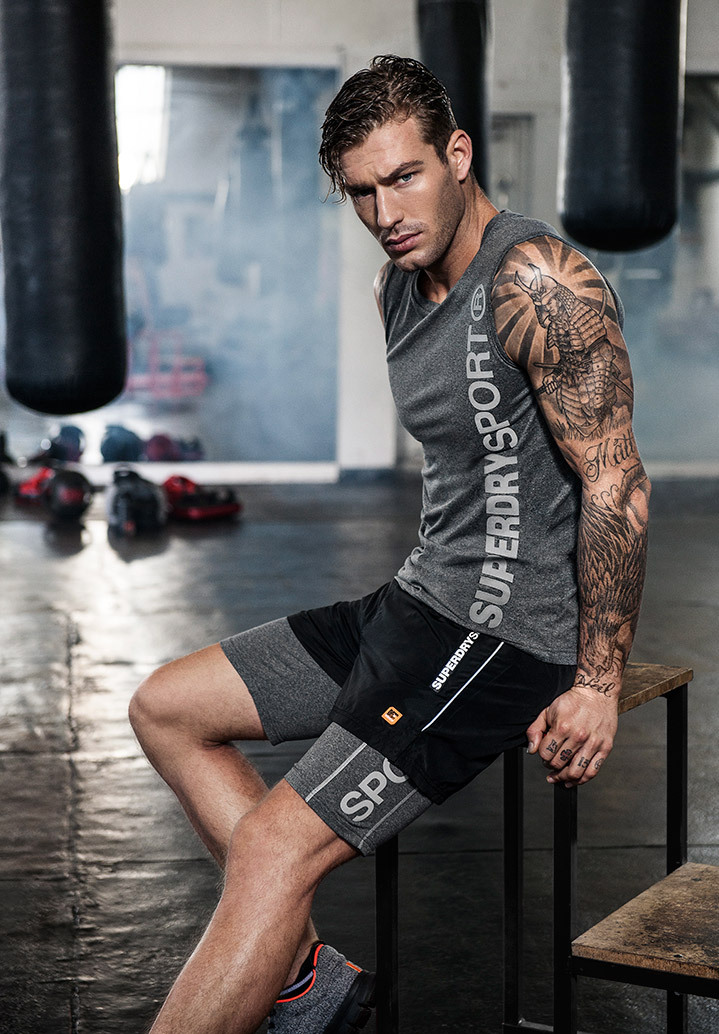 A tattooed fitness model wearing a grey vest, sitting in the gym after a workout