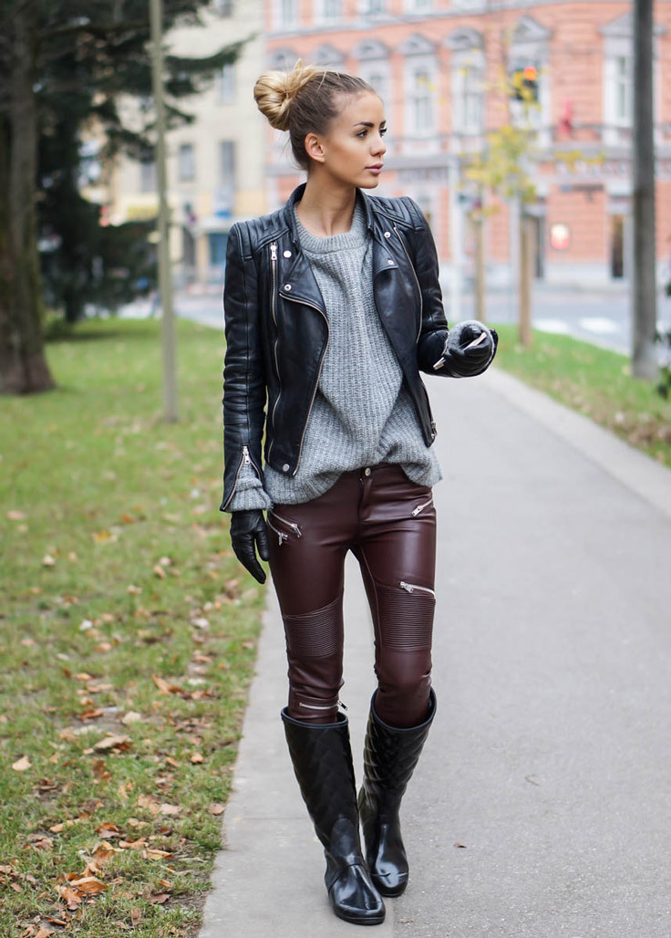 A girl wearing a black leather jacket, a grey sweater and some burgundy leather-look leggings