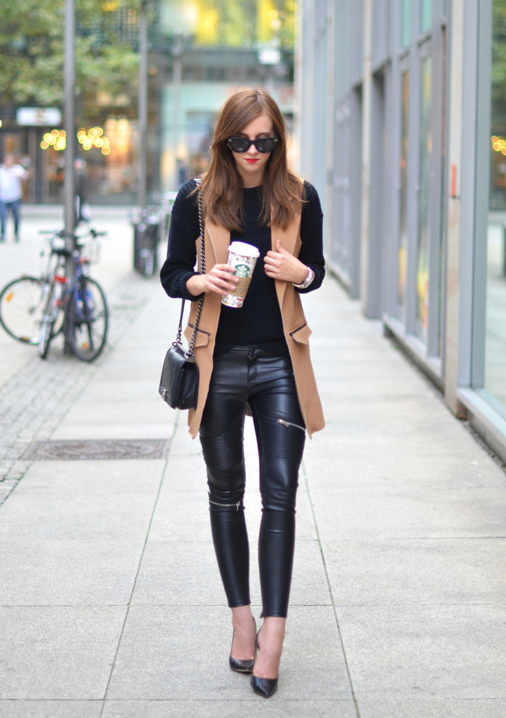 A girl walks down the street wearing a long tan waistcoat, leather leggings and sunglasses