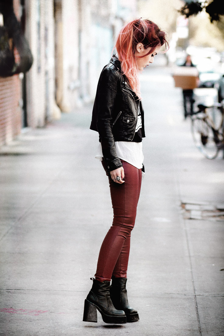 A red haired woman wears a leather jacket and leather  leggings for an edgy street style