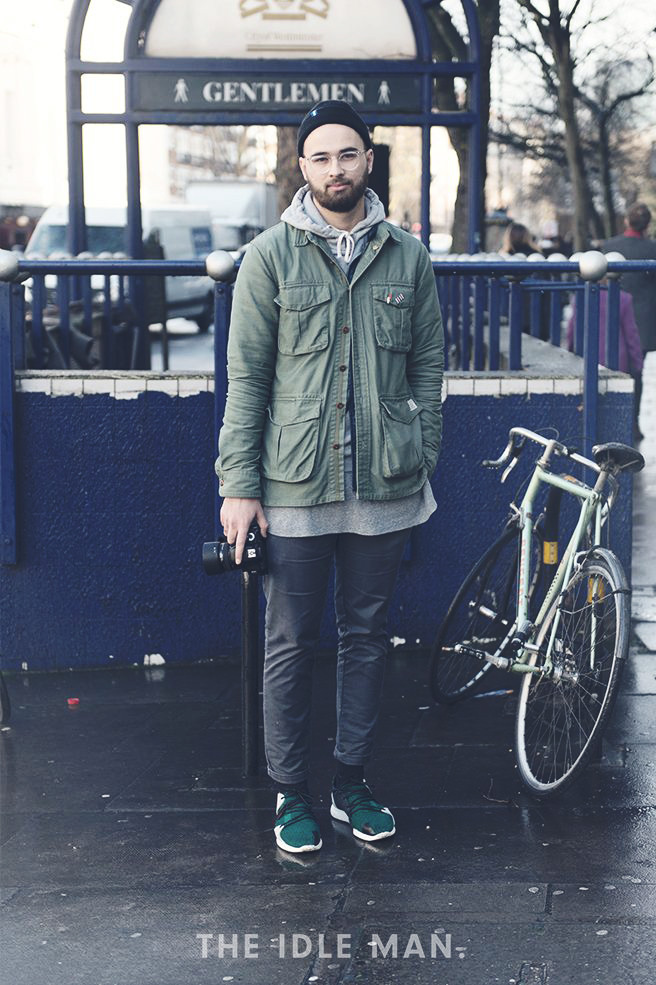 A man wears a hoodie layered with a jacket and styled with dark jeans and green sneakers