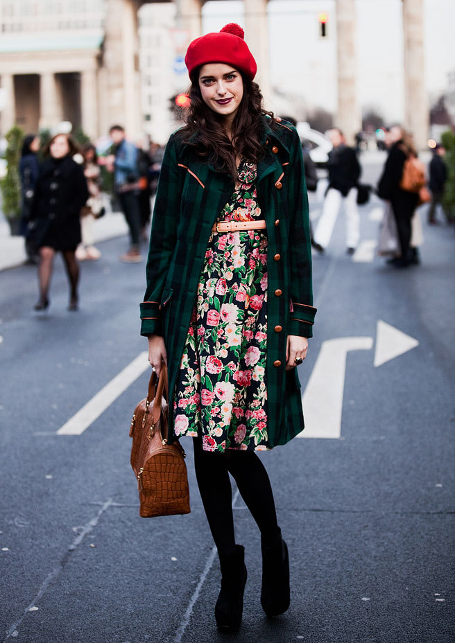 A brunette woman wears a red beret and cute floral dress with a green coat and clashing spring colors