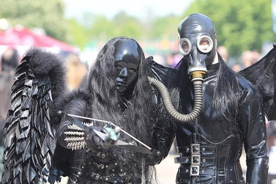Two people wearing Gothic fetish costumes, with black gas masks and dark, gothic wings