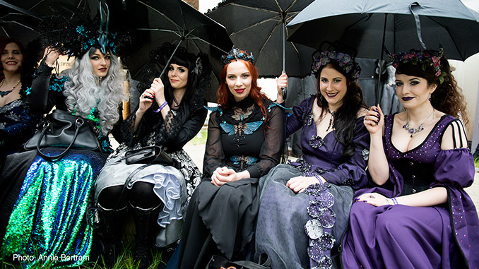 Ladies wearing Victorian Gothic costume, with parasols and full gothic gowns