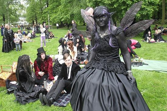 A dark fairy enjoys Wave Gotik Treffen festival, in full costume at one of Leipzig's many parks