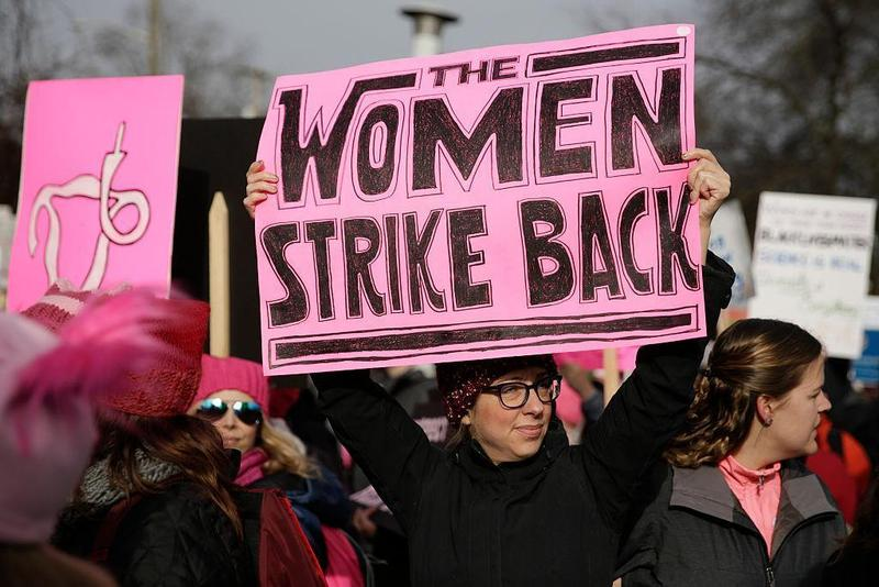 A woman holding a sign reading 'women strike back' as part of women's protest