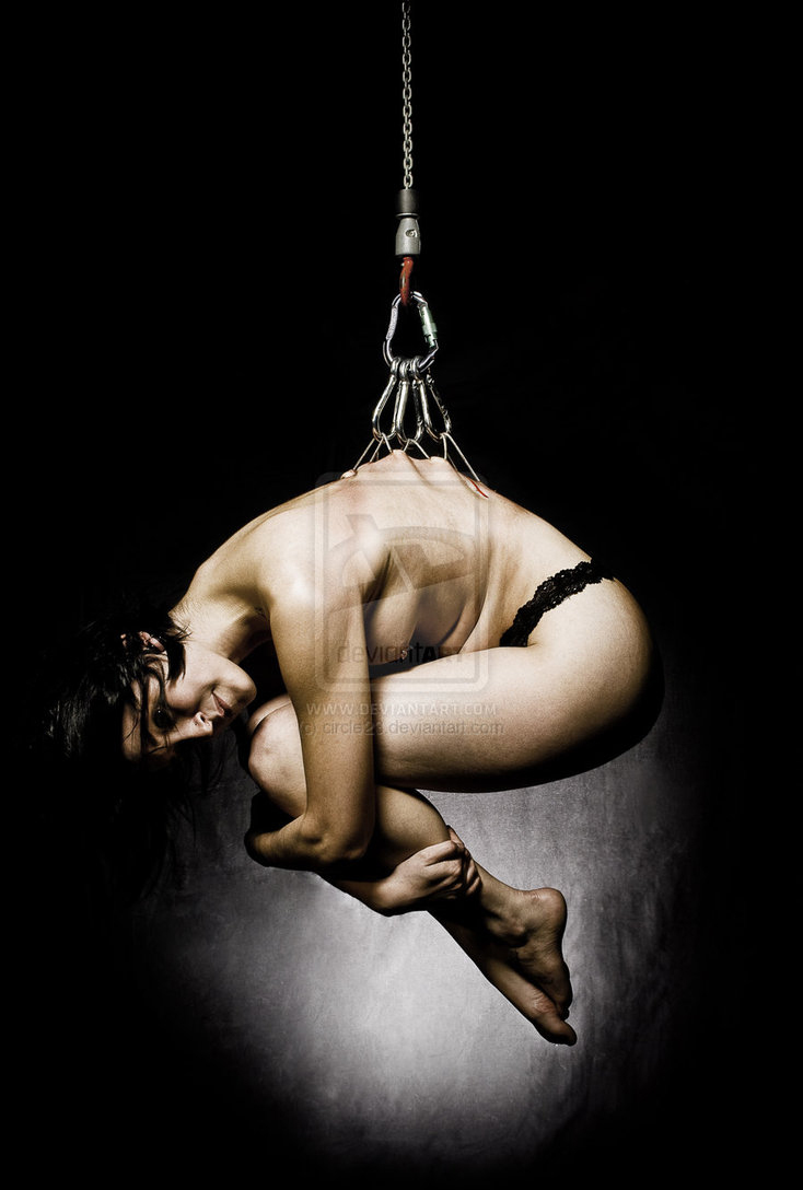 A woman practices body suspension, with hooks through the flesh of her back, being suspended from the ceiling