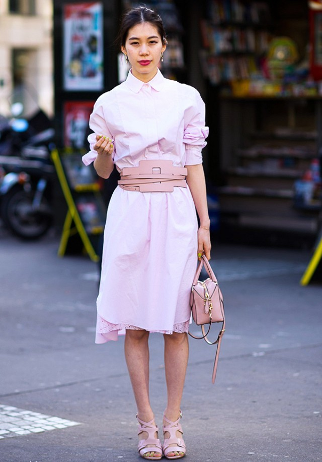 A woman wears a pink shirt dress paired with a chunky, waist-cinching belt