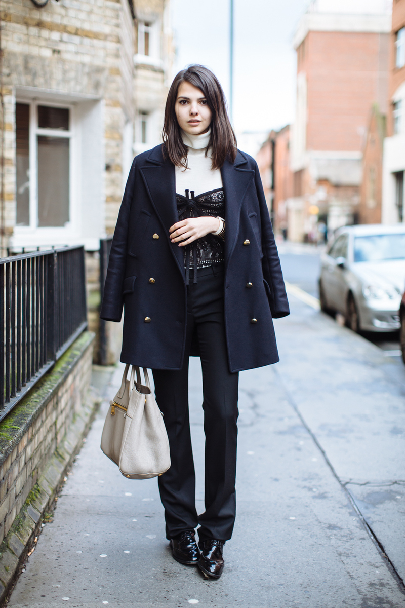 A brunette model wears a layered spring outfit with a corset over a sweater, and a dark winter coat with dress pants