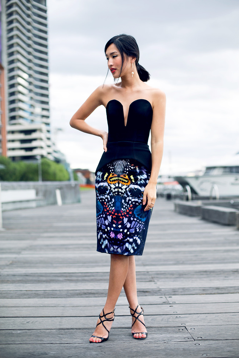 A deep plunge corset in black, paired with a vibrant printed pencil skirt and high heel sandals