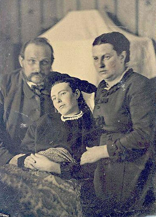 Image of Victorian post-mortem photography, a mother and father with their deceased daughter