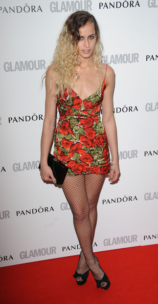 A nighttime sleaze fashion look from Alice Dellal with a floral dress and fishnets with open toe shoes