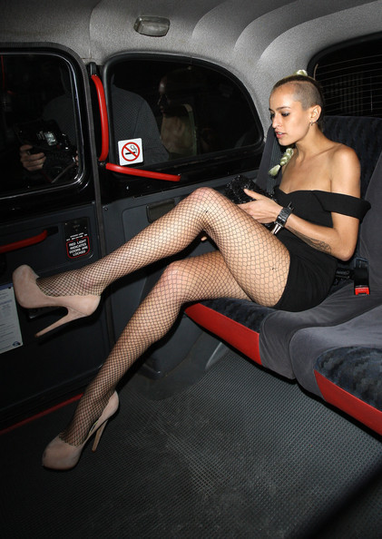 Alice Dellal wears an understated punk outfit with black fishnet tights and an edgy bodycon dress