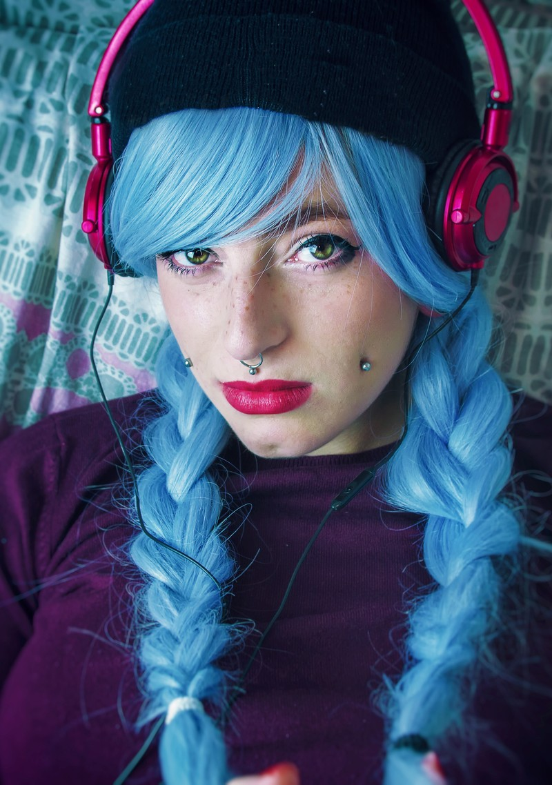 Blue dyed hair, facial piercings and pink headphones